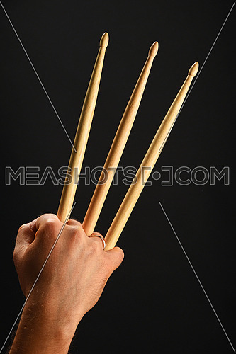 Famous wolverine claws heroic gesture, man hand holding three wooden drumsticks over black background, back view, vertical