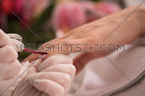 Woman hands receiving a manicure in beauty salon. Nail filing. Close up, selective focus.