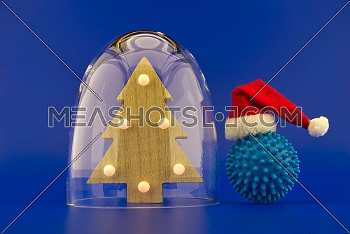 Christmas tree under protective shield as a concept of holidays during covid pandemic and self-isolation, with the ball of corona virus in santa hat outside the glass dome