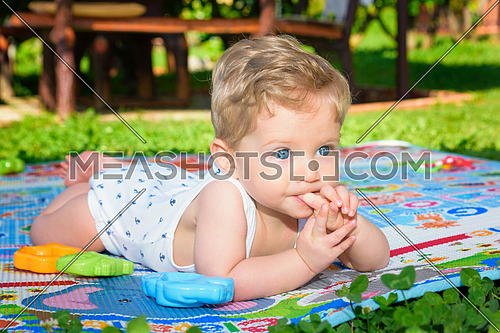 Beautiful baby boy eight month old crawling in the garden with finger in mouth ,close up.