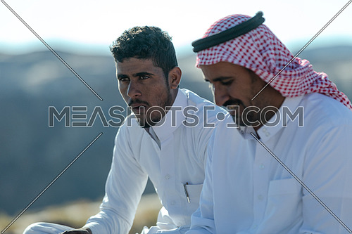Bedouin Males wearing traditional clothing, sitting and eat at Ain Hodouda area in Sinai at day.