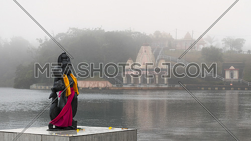 Hindu staue in a famous temple (Grand Basin), background temple,in the day with mist for create mystical atmosphere.Mauritius
