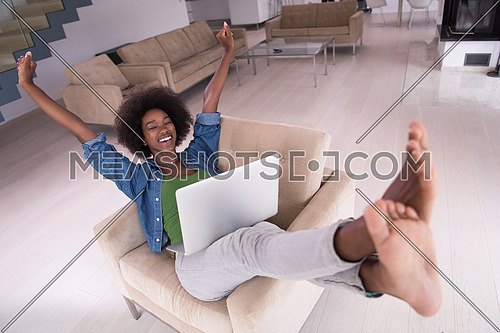 Young african american woman at home in the chair relaxing in her luxury lliving room reading  laptop PC surf internet and work