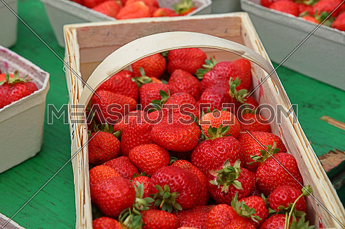 Close up red ripe fresh strawberry with green leaves in big wooden basket crate on retail display of farmers market stall, high angle view