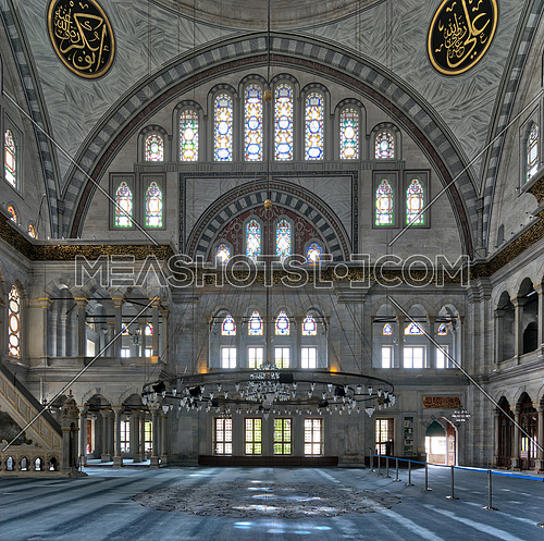 Interior facade of Nuruosmaniye Mosque, an Ottoman Baroque style mosque completed in 1755, with a huge arch & many colored stained glass windows located in Shemberlitash, Fatih, Istanbul, Turkey