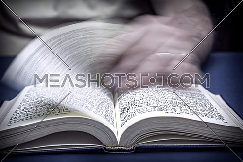Man turns the page in an old little bible or book