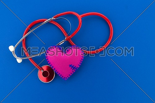 Medical concept with stethoscope and red heart with copy space over blue