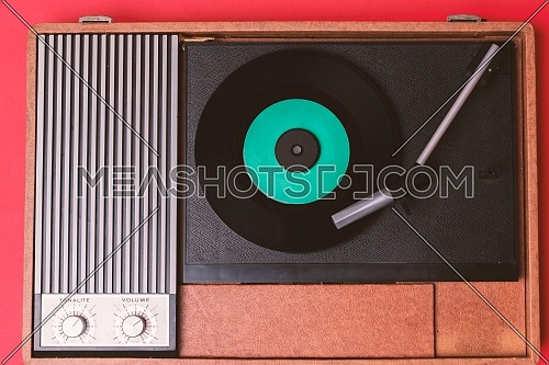 Retro vinyl player and turnable on a red background. Entertainment 70s. Listen to music. Top view.