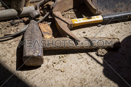 Rusty tools lying on an old dusty workbench with a mallet and hammer in the foreground