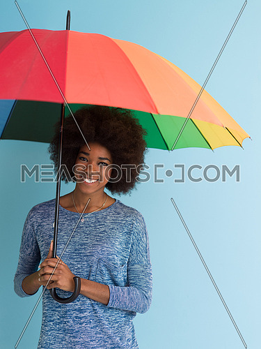 Portrait of young beautiful african american woman holding a colorful umbrella isolated on a Blue background