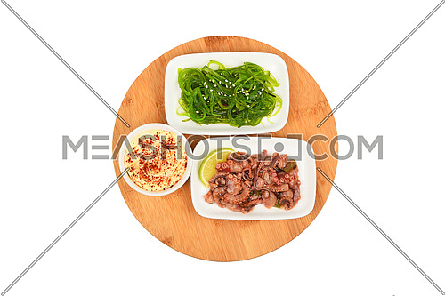 Two portions of seafood marinated salad with squid calamari and seaweeds in with sauce on round wooden board, top view