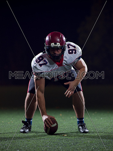 American football player starting football game on american football field at night