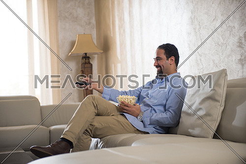 young middle eastern man enjoys with remote control and popcorn on the sofa