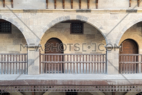 Front view of three arches with interleaved wooden balustrades at the arcade surrounding the courtyard of caravansary (Wikala) of Bazaraa, Medieval Cairo, Egypt