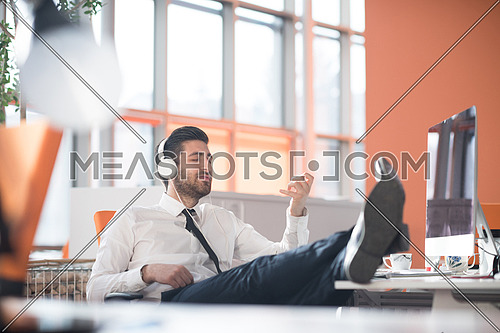 happy young arabian  business man with beard  listening music on headphones at modern startup office