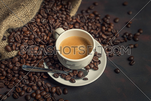 White cup of coffee and coffee bean on dark background. Copy space.