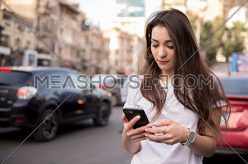 A young woman walking on the street talking in the mobile phone