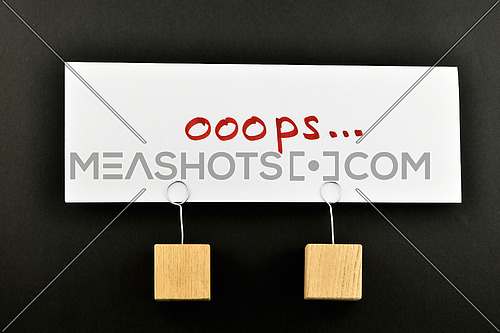 Oops, one big white paper note with two wooden holders isolated on black paper background for presentation