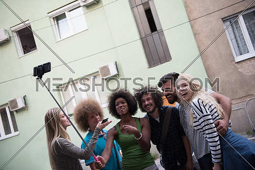 Multiethnic Group of friends taking picture of themselves with smartphone