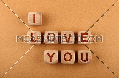 Wooden cube signs with I LOVE YOU words over over background of brown kraft paper with copy space, elevated top view, directly above