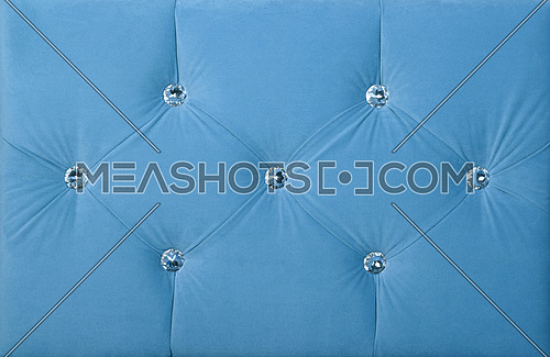 Close up background of pastel blue color soft velvet bed headboard with rhinestone crystals, front view