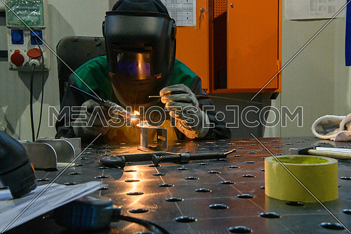 Professional welder performs work with metal parts in factory, sparks and electricity. Industry worker banner. High quality photo