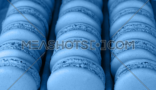 Close up fresh baked blue macaroon pastry cookies (macarons, macaroni) in retail store display, high angle view