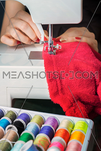 Young woman sewing fabric on sewing machine,sewing process in the phase of overstitchin,colored spools.