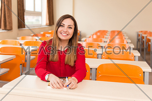 Portrait Of Young Female College Student With Book Sitting In Classroom Alone