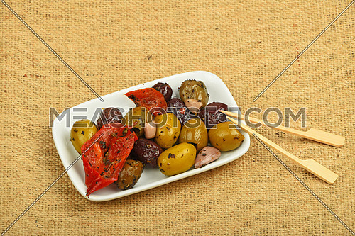 White plate of Mediterranean snack of red and green olives and pickled red pepper with skewers on burlap jute canvas