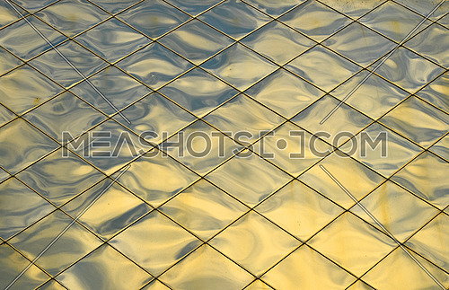 Golden metal shiny vivid rooftop tile panels texture background with reflections, shadows and highlights