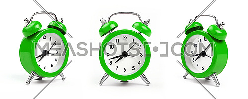 Three small green metal alarm clock with red bells over white background, close up, low angle view in different perspectives