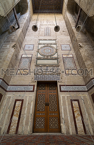 Old decorated stone wall with an ornate wooden door in Al Rifaii mosque, Cairo, Egypt