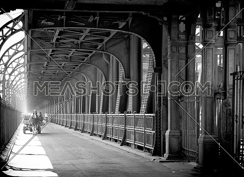 Imbaba bridge in Cairo with a man riding a horse carriage towards the camera