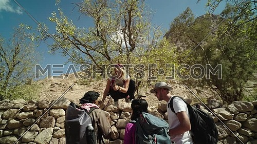 Reveal shot for group of tourists and one climb down fence of rocks eating almonds from tree with bedouin guide showing almond trees while explore Sinai Mountain for wadi Freij at day.