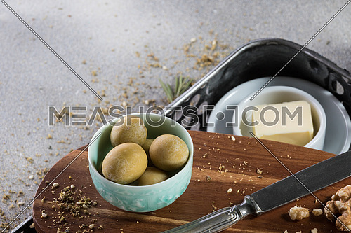A bowl filled w with green Olives and and butter aside with a knife moist with butter and walnuts and rosemary leaves