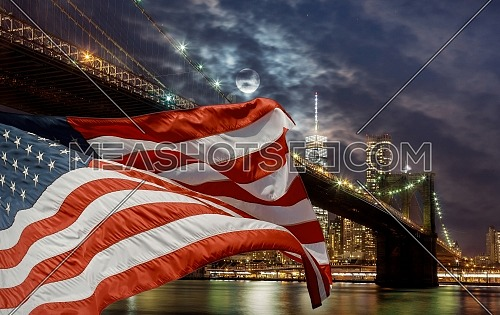 New York City, US Flag flying on Brooklyn bridge at dusk waterfront with Manhattan skyline in the background