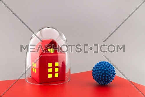 Red building with lights in the windows under protective shield as a concept of covid pandemic and self-isolation, with the ball of coronavirus outside the glass dome