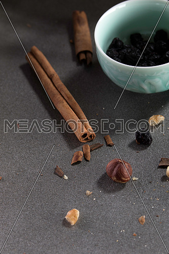 Dry nuts crumbs and cinamon sticks on a grey background