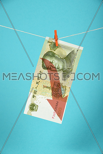 China economy crisis, decline of Chinese yuan, one yuan banknote with red arrow down hanged descending with pin at rope over blue background
