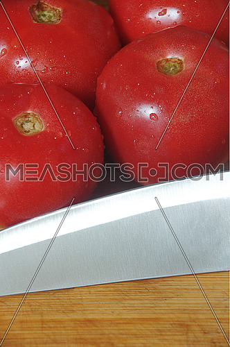 ripe fresh tomatoes with knife over a wood cutting board