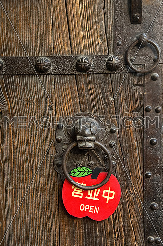 finely decorated chinese wooden old door with a red open sign