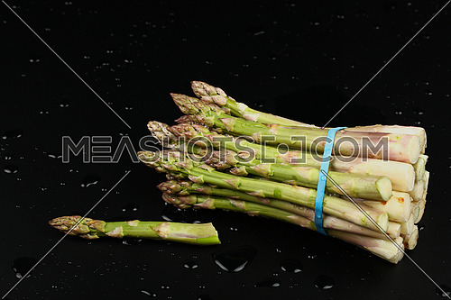 Close up bunch of washed fresh green asparagus on black table with drops of water, high angle view