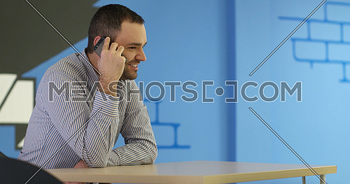 relaxed young businessman using smart phone at modern startup business office