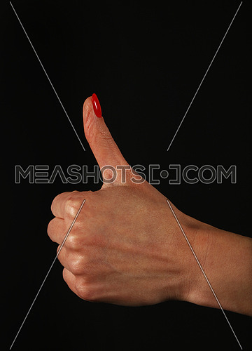 Woman hand with red nails showing thumb up, like, ok or good gesture isolated on black background, side view