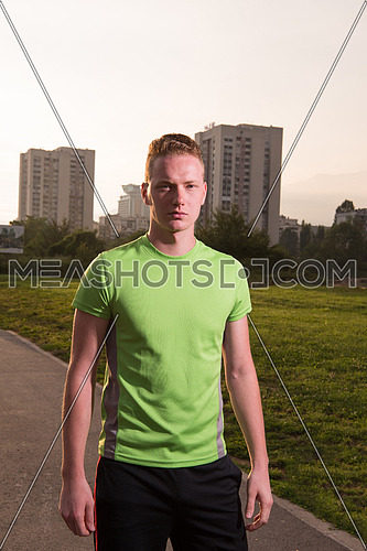 Young man looking at the rest of path during a break of his outdoor jogging training