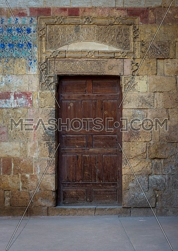 Old wooden door framed by bricks stone wall at the courtyard of al Razzaz historic house, Darb al Ahmar district, Old Cairo, Egypt