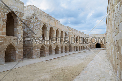 Aged building of stone blocks with archs and windows on cloudy day, Qaitbay Citadel, Alexandria, Egypt
