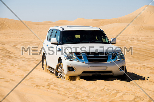 a white SUV stuck in the desert sand