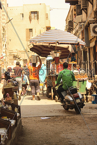 The famous Al Moez street in old Cairo, EGYPT showing people walking in their busy lives and a man on a scooter